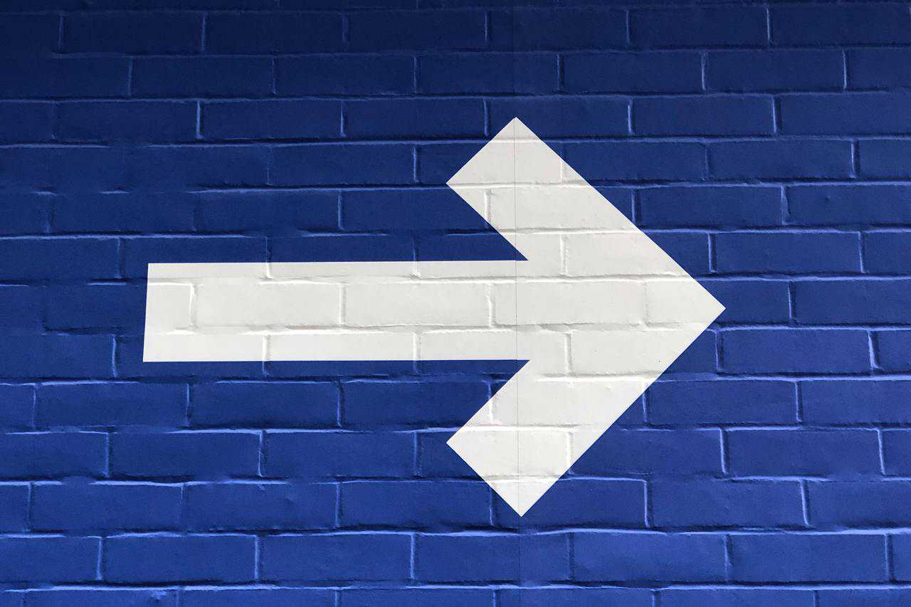Arrow sign on blue wall