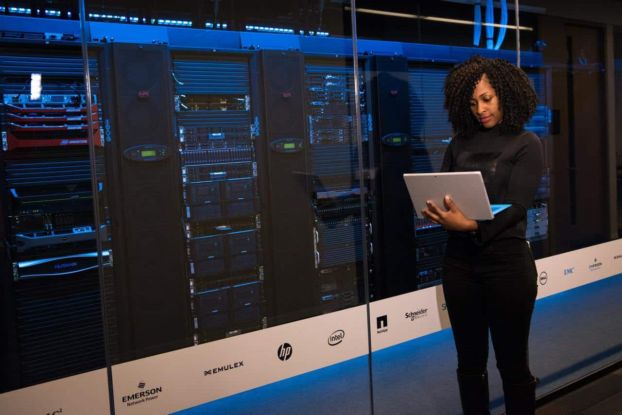 Woman in server room with laptop