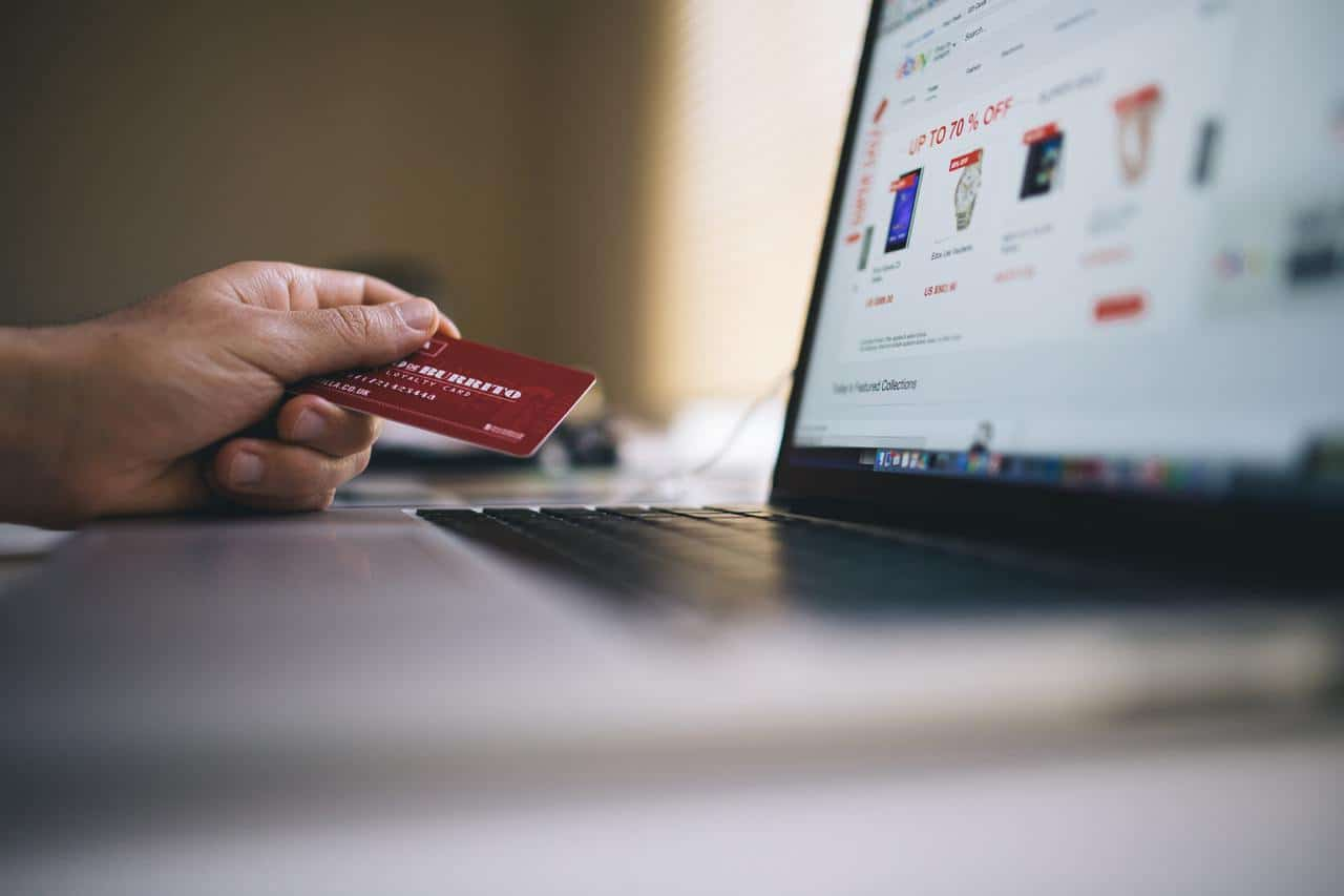 Person holding credit card while online shopping