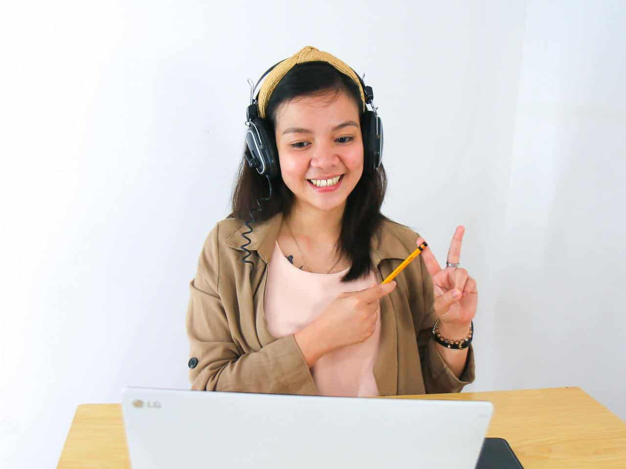 Woman showing peace sign to laptop camera