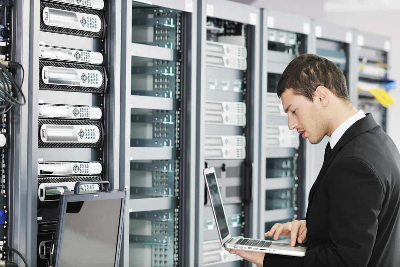 Man looking at laptop in server room