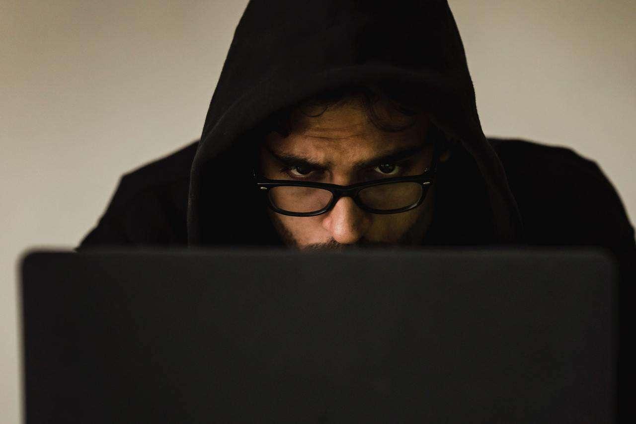 Man in hoodie using laptop